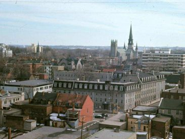 A view of the Convent of our Lady of the Sacred Heart, colloquially known as the Rideau St. convent, as it appeared in 1968, looking south across Rideau St. The convent faced Rideau St. and occupied the block between Waller, Besserer and Cumberland Sts. The convent was demolished in 1972 and the site is now occupied by the Claridge Towers. The convent's chapel was saved, however and is now on display at the National Gallery of Canada. In the background, one can see St Joseph's church and, behind it, the second Sacré Coeur church, with its very high steeple, which burned down in 1978. Source: CMHC